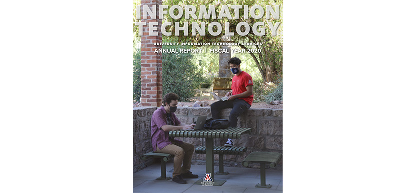 cover of the annual report - 2 students working on laptops at Old Main