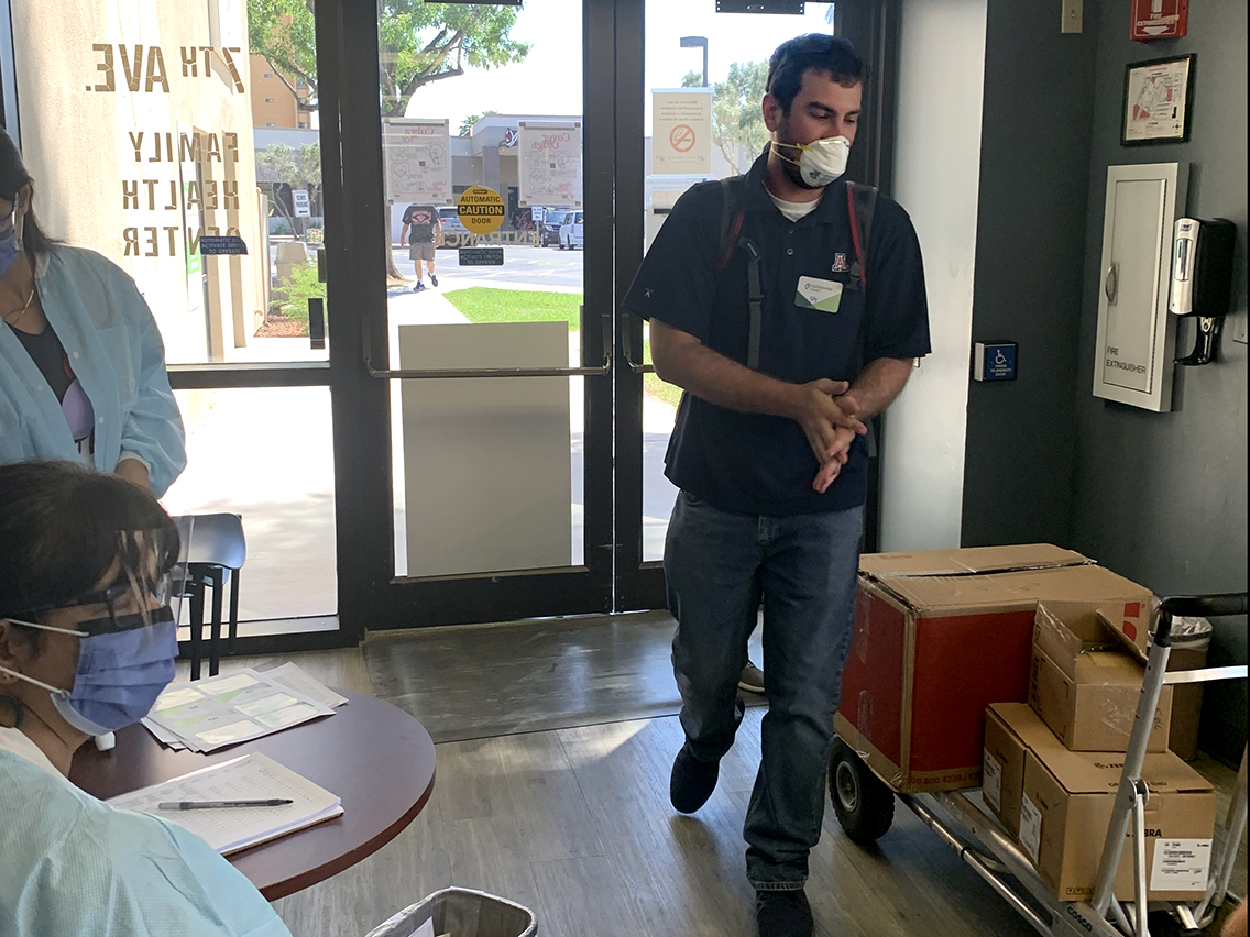 Collin Rogow brings a load of equipment into a Valleywise Community Health Center in Phoenix