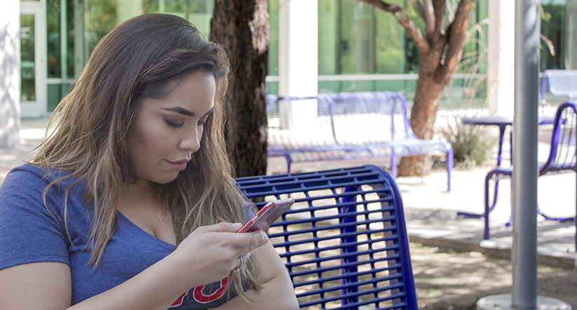 a student browses the Arizona Mobile app on her smartphone