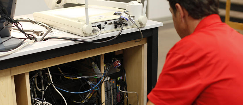 An image of a technician setting up a classroom computer