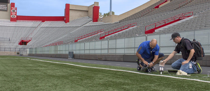 An image of technicians preparing communications equipment on the football field