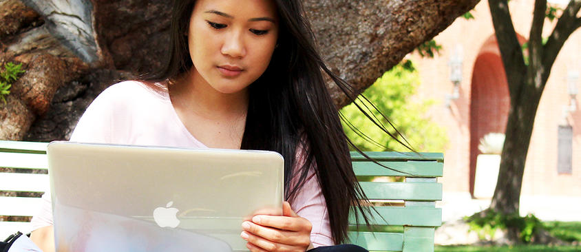 An image of a student working outside on her laptop