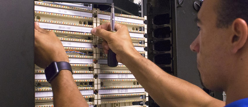 An image of a technician working on network equipment