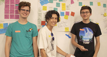 Three students pose with board of post-it notes capturing their freshman memories